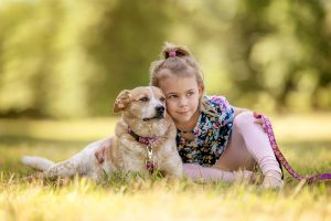 A girl and her dog spend a quiet moment in a meadow