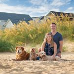 Dogs and their people pose on on a sandy dune